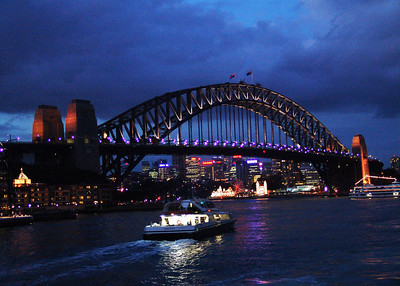 Sydney Harbour Bridge with Luna Park illuminated in the background as seen from Circular Quay wharf