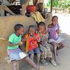Children next to the kitchen hut for their family, Sindie, near Livingston, Zambia, 4/6/2014