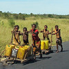 Young boys pushing carts with water on the main highway to their homes.  Madagascar, 4/17/2014