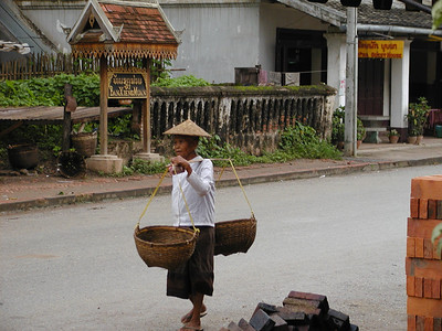 Old Woman Carrying Baskets on Her Shoulder
