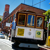 Cable Car outside the Cable Car Barn.  Note the window reflections on the right of a Victorian House and the middle window reflecting the TransAmerica Building
