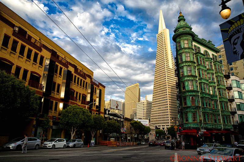 The TransAmerica Building and the Columbus Tower or Sentinel Building built in 1907.   The copper-green  flatiron style structure is optically much larger than in reality