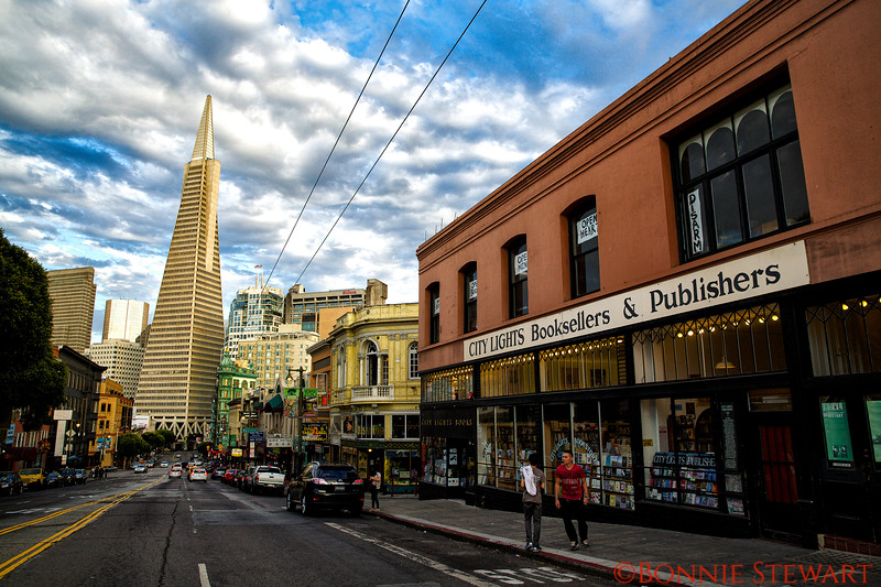 The TransAmerica Building and the Columbus Tower, also known as the Sentinel Building, showing the difference in size.  The Columbus Tower was built in 1907 and was one of the first skyscraper's in the City.  The City Lights Bookstore was the first all-paper back bookseller in the country.