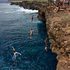 Swimmers jumping off the cliffs at Ka Lae (South Point) Hawaii.