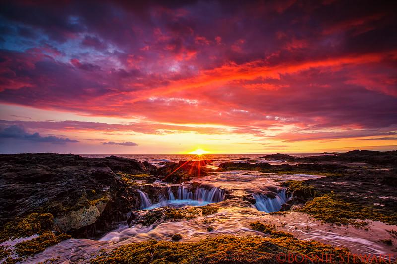 Hawaii sinkhole at sunset with a sunburst