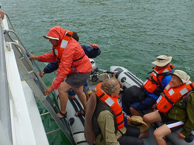 We  climb down a ladder into a swaying small inflatable boat.