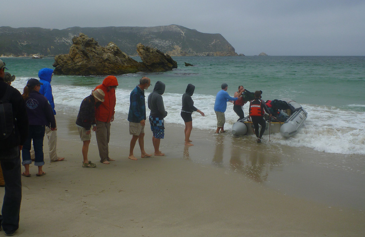 After landing, the gear is brought ashore using a human chain.