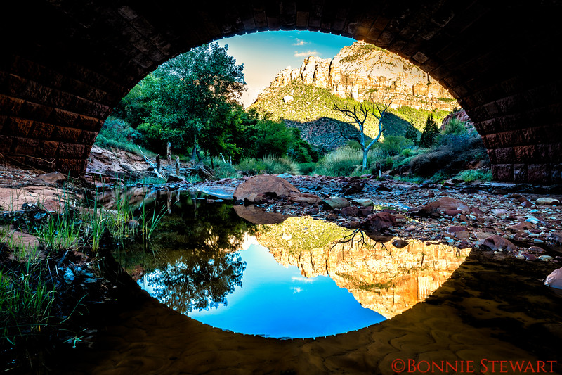 "View under a bridge towards the ""Watchman"" with river reflections"