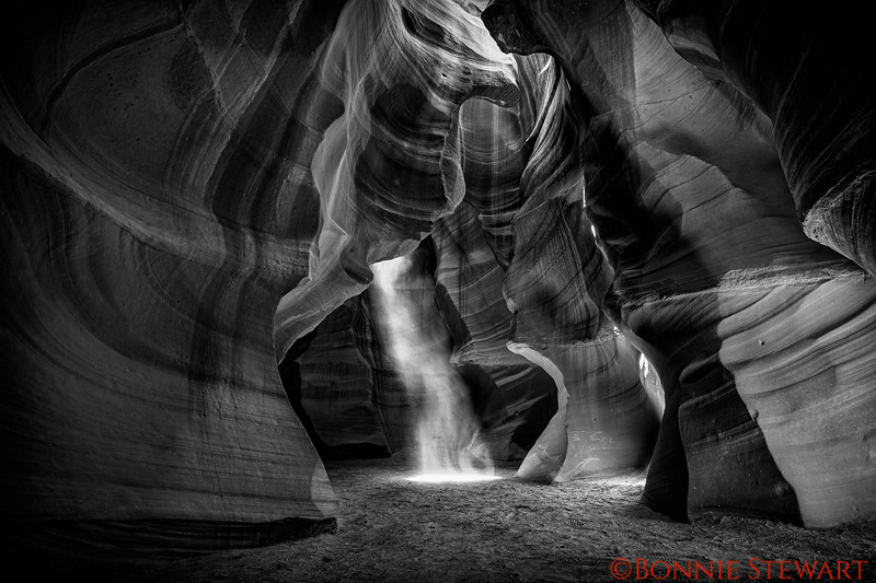 A Black and White image of the Light entering the canyon and highlighting the sand.