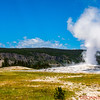 Old Faithful erupts with the Old Faithful Inn in the background