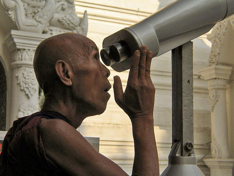 Curious monk, Shwedagon - A Buddhist monk enjoys a surprise while studying the spires of Shwedagon through a powerful telescope. There are over 800,000 monks in Burma. At one point in their lives, nearly all Burmese men spend some time as a monk. Very few serve more than a few years, however.