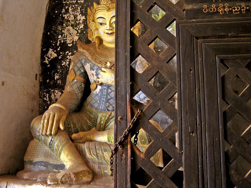 Inside Ananda, a glimpse of Buddha - A Buddha image peers from behind a door within the ruins of Bagan's ancient Ananda Temple.