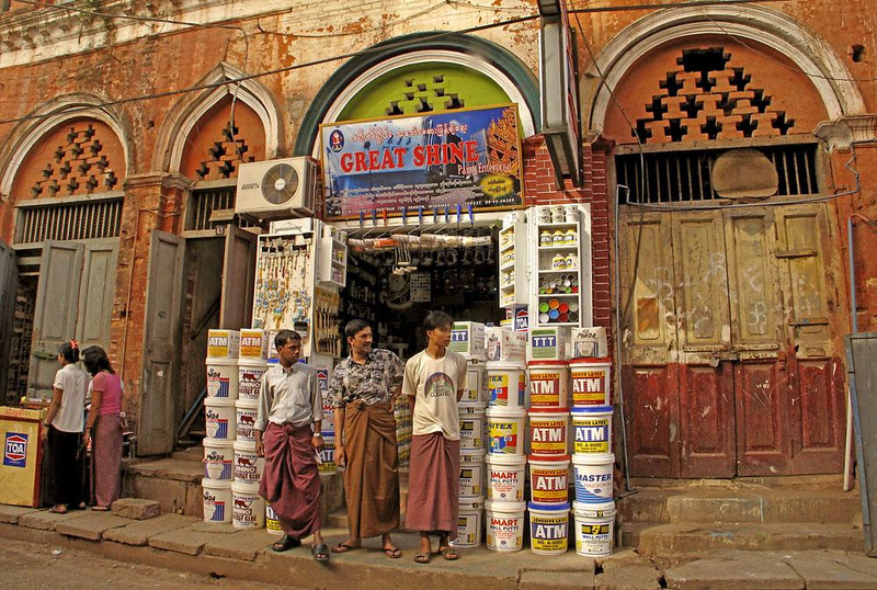 Paint Store, Indian Quarter, Yangon - Three salesmen await customers in front of their paint store, located in a building that has seen empires rise and fall in Old Rangoon. The men wear the longyi sarong, the Burmese national costume for both genders. Men tie the sarong in front. Women tie it into a waistband on the side.