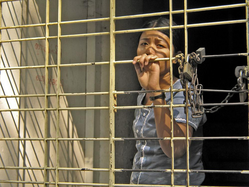 Lock down, Yangon - Most of the people I saw on the streets of Yagon seemed relatively comfortable with their daily lives. This woman, however, looking out at me from within a caged doorway, was an exception.