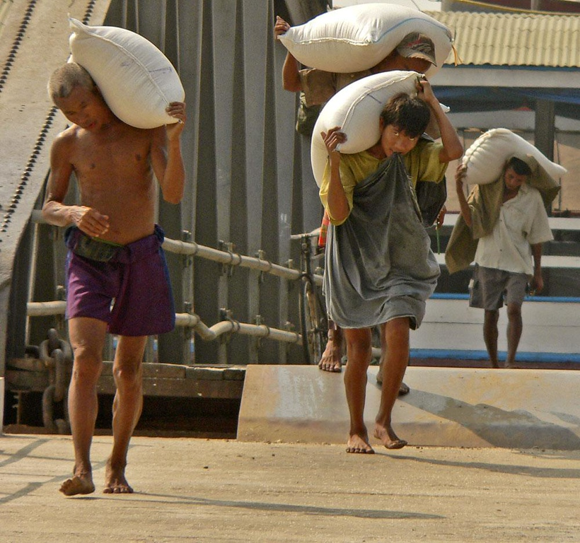 Unloading Rice at the Yangon Jetty - Young men, some of them very young, carry huge bags of rice from ship to shore on Yangon's jetty. They apparently are paid by the bag, because they move very quickly.
