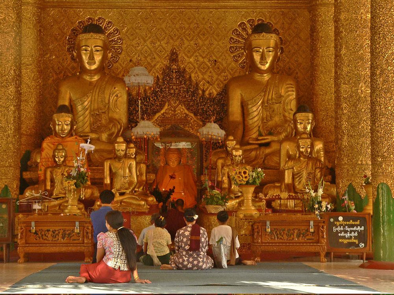 Eleven Buddha Images at Shwedagon - Thousands of visitors express their faith in Buddhism at Shwedagon every day. Here a family prays before an altar of eleven Buddha images. It has often been said that Burma is the most profoundly Buddhist country in the world.