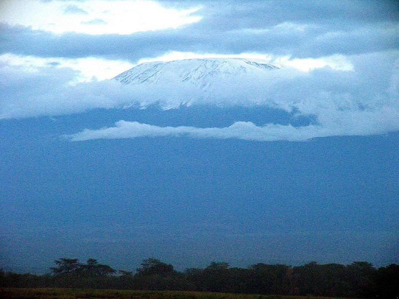 Kilimanjaro shows its snow - The 19,340 foot summit of Mt. Kilimanjaro, Africa's highest mountain, is usually wreathed in clouds. They sometimes part for a few moments just after sunset, revealing the snows that inspired Ernest Hemingway's short story.