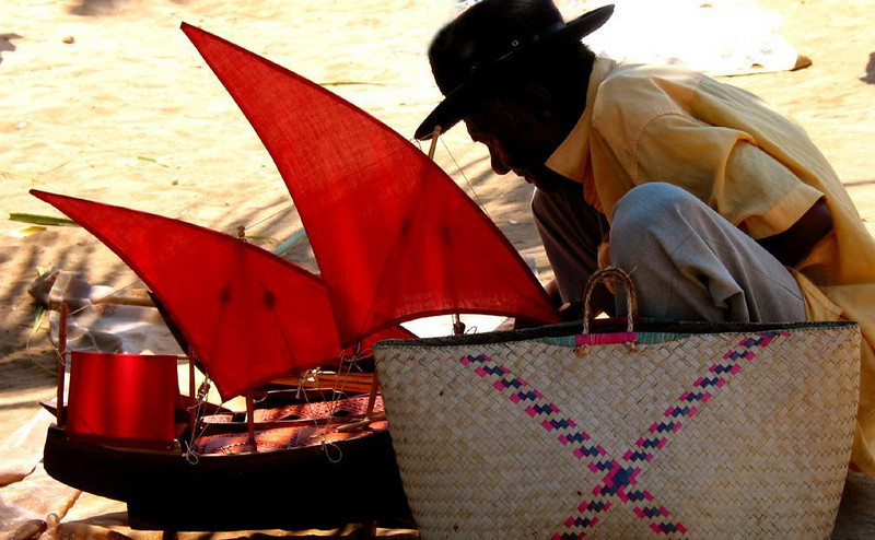 Madagascar Craftsman - A model-maker works on his rendition of Madagascar's distinctive fishing boats at the beach in Nosy Kombo.
