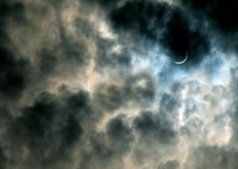 "The Crescent Sun - The clouds are illuminated by a sliver of the sun, as the eclipse nears ""totality""."
