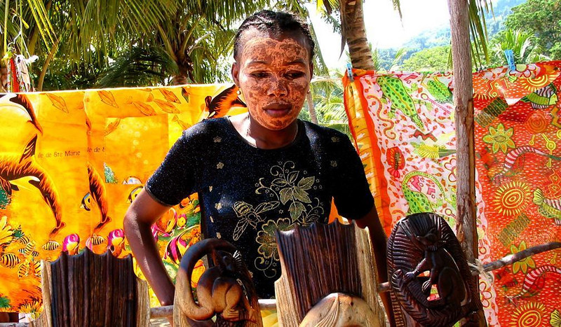 Decorated Saleswoman - The sales people embellish themelves as lavishly as their goods in the village of Ampangoriana on the island of Nosy Kombo, Madagascar