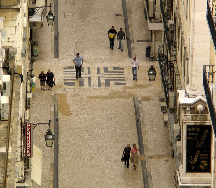 Lost in Lisbon? - I shot this scene from the top of Lisbon's famous, if somewhat battered, Elevador de Santa Justa. The iron elevator was built about 100 years ago by one of A.G. Eiffel's apprentices. Both this and the previous image were made from the tiny viewing deck on top of the elevator. There are eight people walking up Rua Santa Justa in this photo. Seven of them seem to know where they going. One, however, does not. It's easy to get lost in Lisbon -- its streets start and stop without notice, disappear into plazas, and climb around hills, all of which makes it one of the most invigorating walking cities in the world.