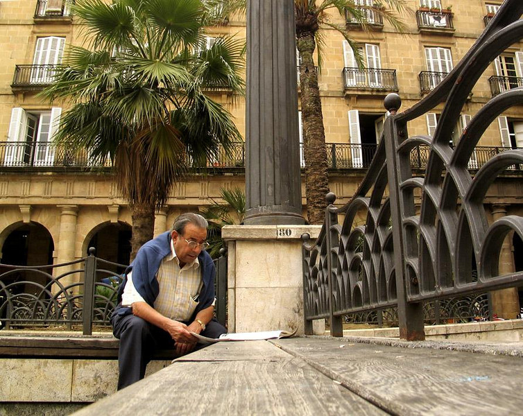 Plaza Nueva, Bilbao, Spain - A gentleman of Bilbao catches up on the news at a bench in the Basque city's Old Quarter. Bilbao, founded in 1300, is one of the leading seaports in Spain and a major industrial center.