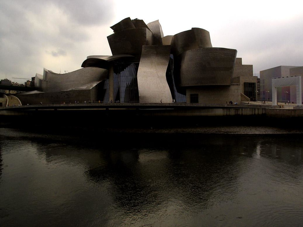 Riverside view, Guggenheim Museum - The Guggenheim has been likened to a beached ship or a gigantic flower. I photographed it from across the Nervion River on an overcast afternoon, when it looked more like a medieval castle wearing 21st century armor.
