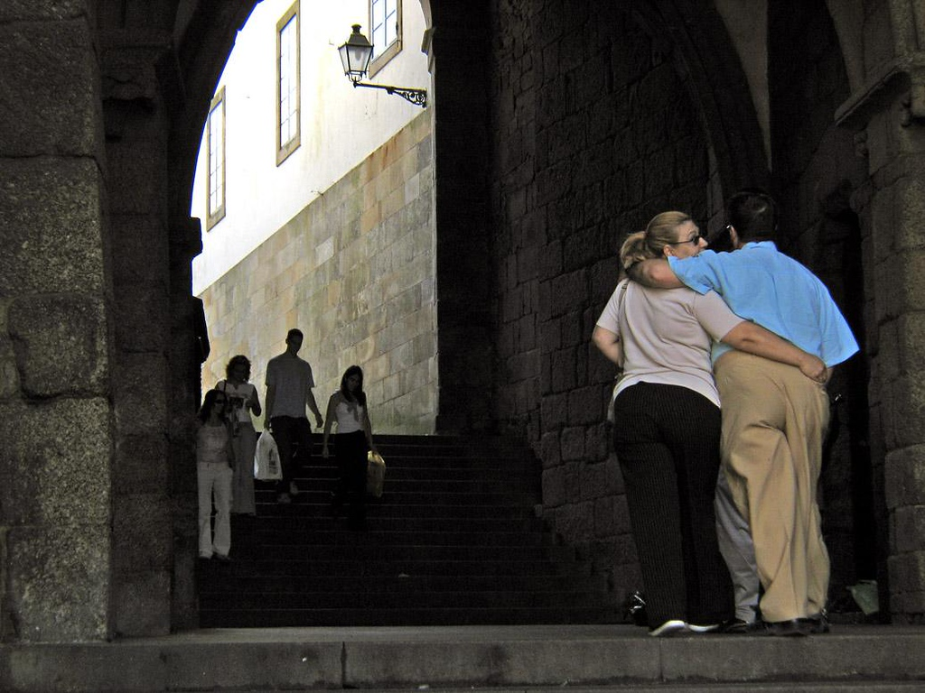 The Hug, Santiago de Compostela - Three people embrace under the arched tunnel leading to Plaza del Obradoiro -- the center of Santiago de Compostela.