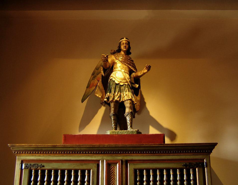 Archangel, Hostel de los Reyes Catolicos - In the lobby of the Hostel de los Reyes Catolicos, now one of the most luxurious state-run hotels in Spain, is a haunting carving of the archangel St. Michael. The Hostel was originally the Royal Hospital, commissioned by Ferdinand and Isabella in 1501 to care for pilgrims who had fallen ill or were tired from their long journey. (Many of them had crawled on their knees to Santiago de Compostela.)