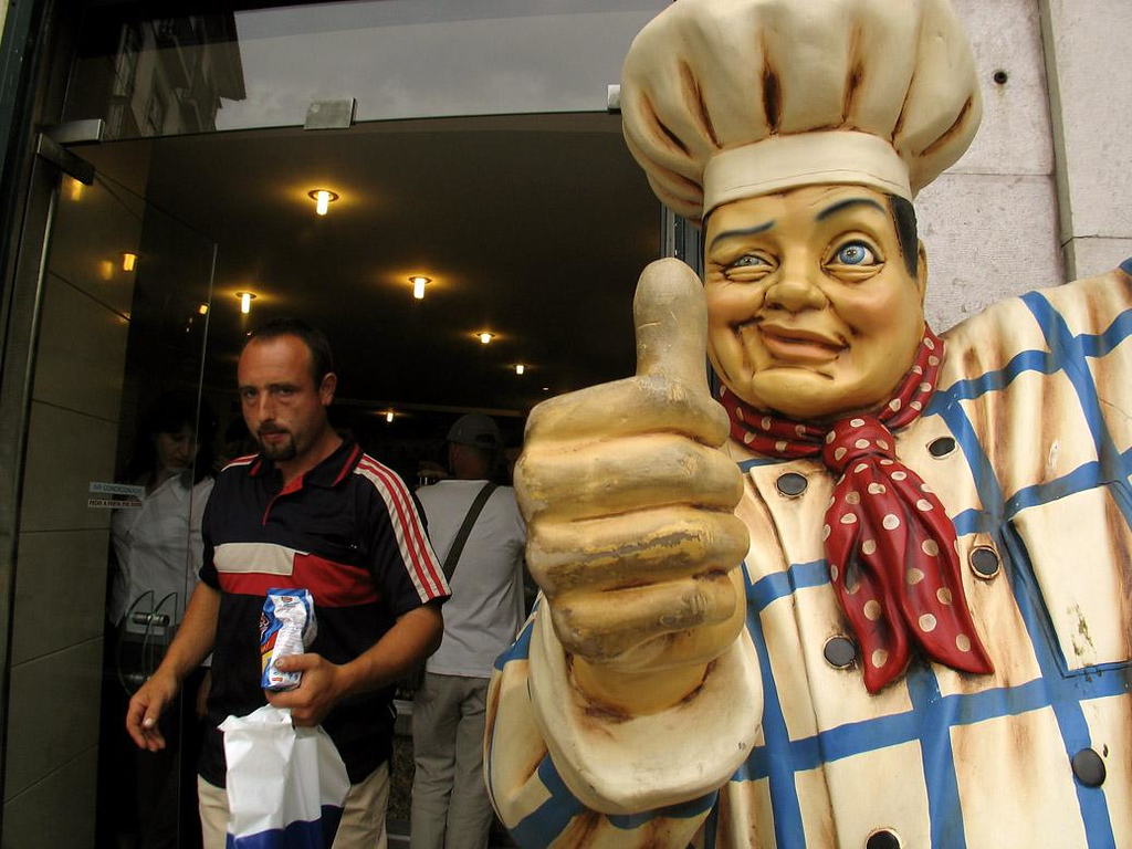 Portuguese Burger, Lisbon - A shopper leaves a burger place with dinner. He doesn't quite seem to be as enthusiastic about it as the big chef.