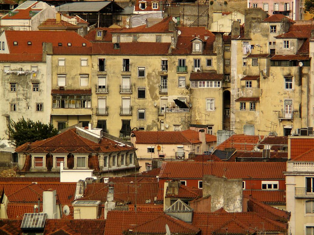A slice of Baixa, Lisbon - The juxtaposition of old tile roofs and hundreds of TV antennas is a common scene in Lisbon. This photograph, which embraces a slice of Lisbon's Baixa neighborhood, was also made from the top of the Elevador de Santa Justa. The buildings running across the middle of the picture display laundry, umbrellas, satellite TV dishes, and windows of every description, and are typical of the 18th and 19th century architecture that gives the city its great charm.