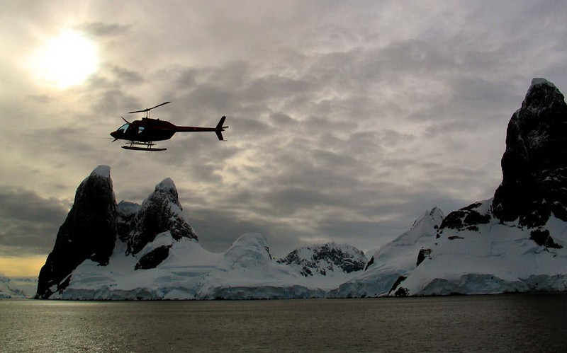Chopper Up, Lemaire Channel - Our ship's helicopter lifts off as we enter the spectacular Lemaire Channel flowing among the islands alongside of the Antarctic Peninsula. It will fly ahead of us, guiding our ship through this beautiful but ice filled passage.