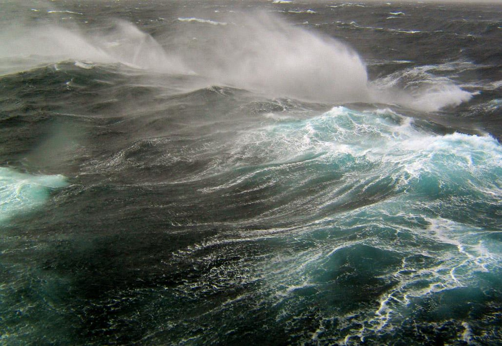 """Riding the Drake Passage - Perhaps the most turbulent wind driven waters on earth are the 600 miles between the southern tip of South America at Cape Horn and the Antarctic Peninsula. In 1578, England's Francis Drake rounded South America in the """"Golden Hind"""" and was hurled backwards into these waves, discovering what we now call the Drake Passage. Winds and waves fly around the globe unhampered by land and pour into this chute. You don't sail the Drake Passage, you ride it."""