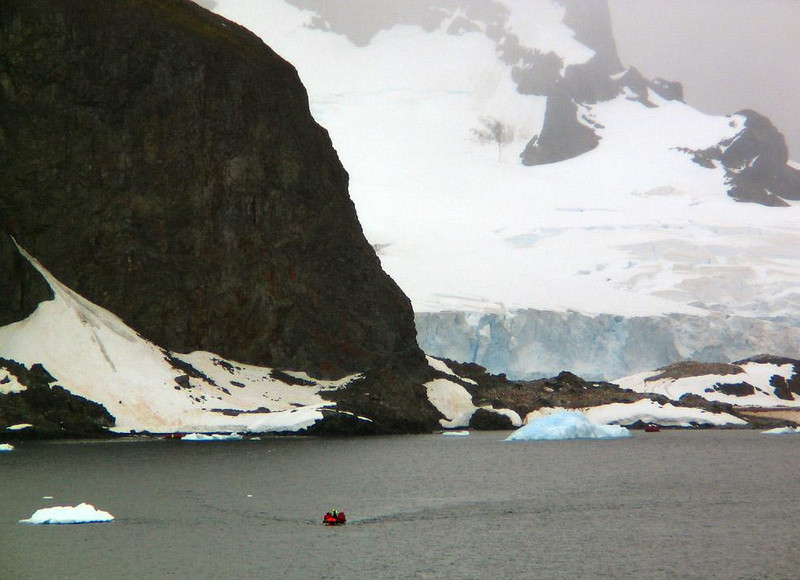 The Great Cliffs of Cuverville Island - Cuverville Island may be small in size but it is staggeringly high. Just how how high it is can be seen by comparing it to the size of one of our Zodiacs heading its way.