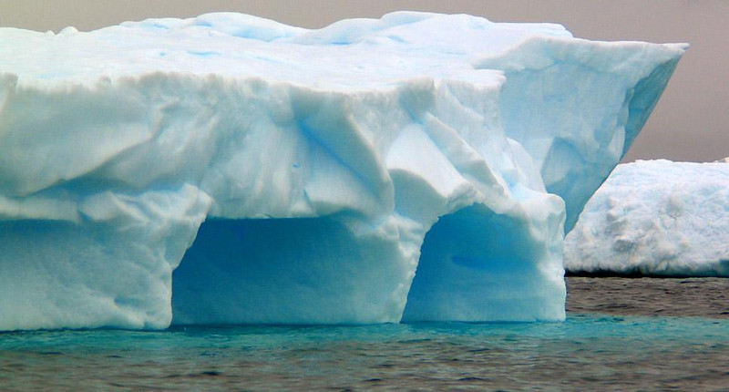 Blue Caves, Cuverville Island - Icebergs surround Cuverville Island, including this one featuring two deep blue caves in it.