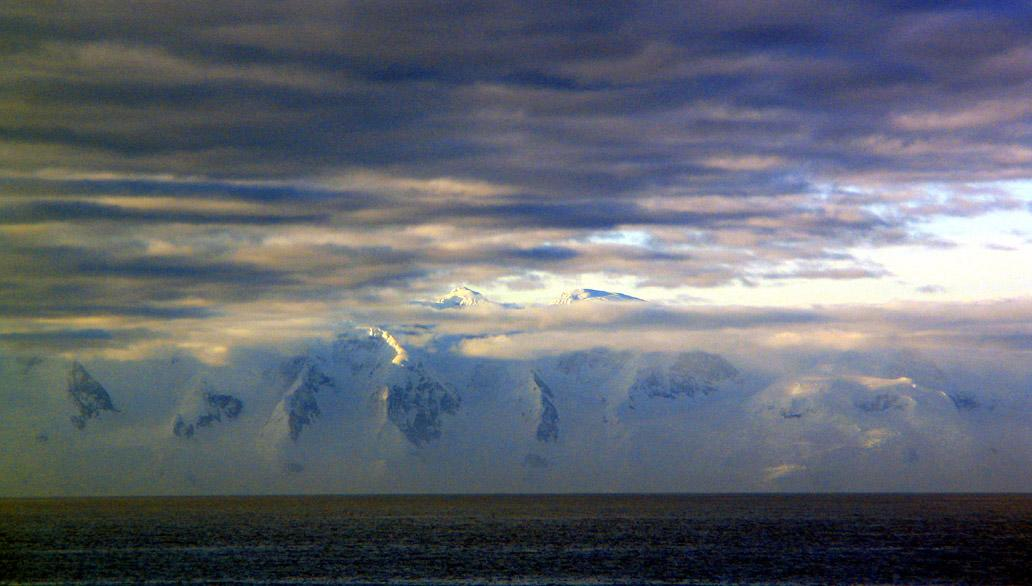 First sighting, Antarctic Peninsula - I could not be sure what I was seeing before me. It looked like a huge fog bank at first, and then the veil of clouds hugging the water began to part, revealing the snow covered mountains of the Antarctic Peninsula.