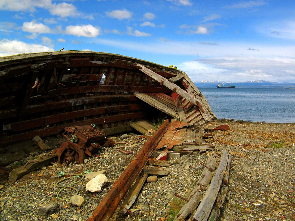 Shipwreck, Ushuaia, Argentina - A gutted boat rots on the beach in Ushuaia. Parts of its engine rust on the ground. In any other town, it would be an eyesore. In rugged Ushuaia, however, shipwrecks are the norm.