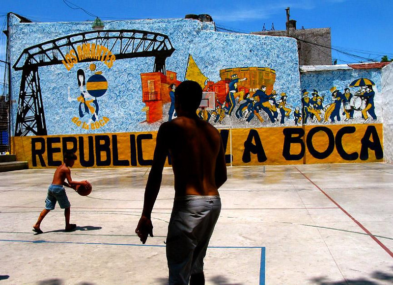 Basketball Court, La Boca, Buenos Aires - The colorful and turbulent wall mural dominates this scene, creating a striking contrast to the actual game featuring only two players.