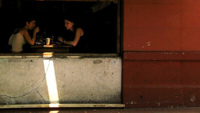 Conversation, Plaza Dorrego, San Telmo - A mysterious shaft of sunlight illuminates this earnest conversation in a small cafe on the Plaza Dorrego in Buenos Aires' San Telmo neighborhood.