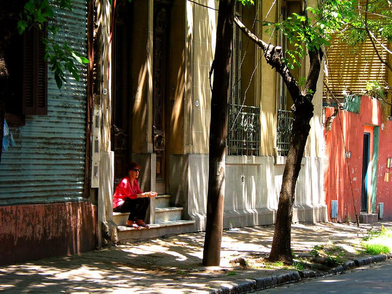 La Boca Street Scene, Buenos Aires - The colorful nature of this neighborhood comes through here as well. The soft colors in a shadowed light provide excellent contrast for the lady in the bright red shirt.