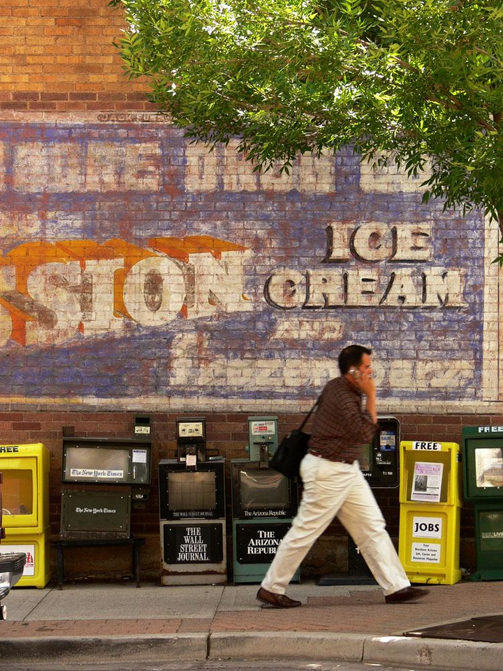 Ice Cream Sign, Flagstaff - As I watched this blur of a man, a cellphone clasped to his ear, rush past copies of The New York Times, The Wall Street Journal, and The Arizona Republic, it occurred to me that if he was in the same spot eighty years ago, he would probably be thinking about a delicious slab of Mission Ice Cream. That fading message from Flagstaff's past overwhelms the scene, but he will never see it.
