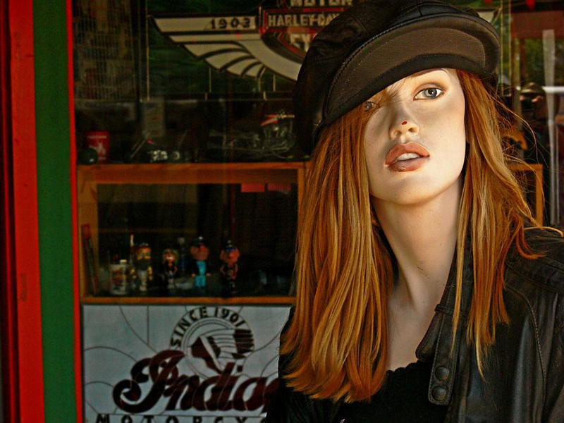 One way conversation in Seligman - Seligman's biker's shop is a popular gathering place. Perhaps it's because the clientele enjoys bantering with this hostess who sits just outside the shop, never moving her lips in return. (The chipped nose and stylized teeth give her away.) From Kingman down to Seligman, old Route 66 still sweeps in an unbroken, seldom-used 58 mile, off-the-beaten-path stretch of historic roadway. No wonder the town has become magnet for the bikers who enjoy conversing with her.