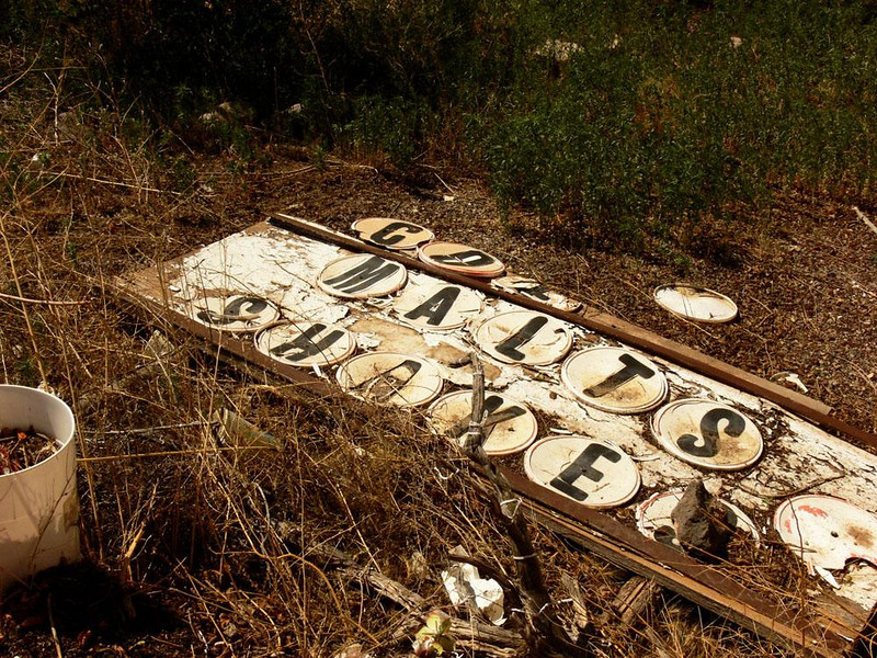Discarded signage, Snow Cap Drive-in - Generations of debris give Seligman's Snow-Cap Drive-in much of its character. How long has this sign that once helped sell malts and shakes to Route 66 travelers, been bleaching in the grass?