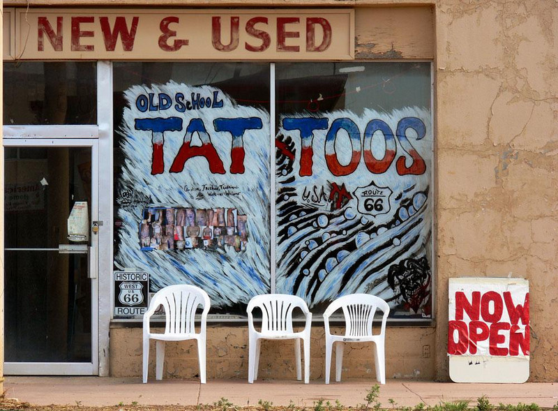 Tattoos, New and Used, in Seligman - Nobody buys cars in Seligman any more. This dealership has become a tattoo parlor, serving the bikers that often rumble along what is left of Route 66. I was drawn to the scene by the juxtaposition of words -- both the old and the new.