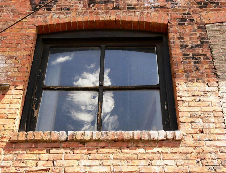 Spirit in a Flagstaff alley - While prowling the side streets and alleyways of this old western town, I noticed what appeared to be a face floating in a window, looking down at me from within a building dating back to the town's founding. Logic tells me this is just a reflected cloud. But what I feel in this image tells me otherwise.