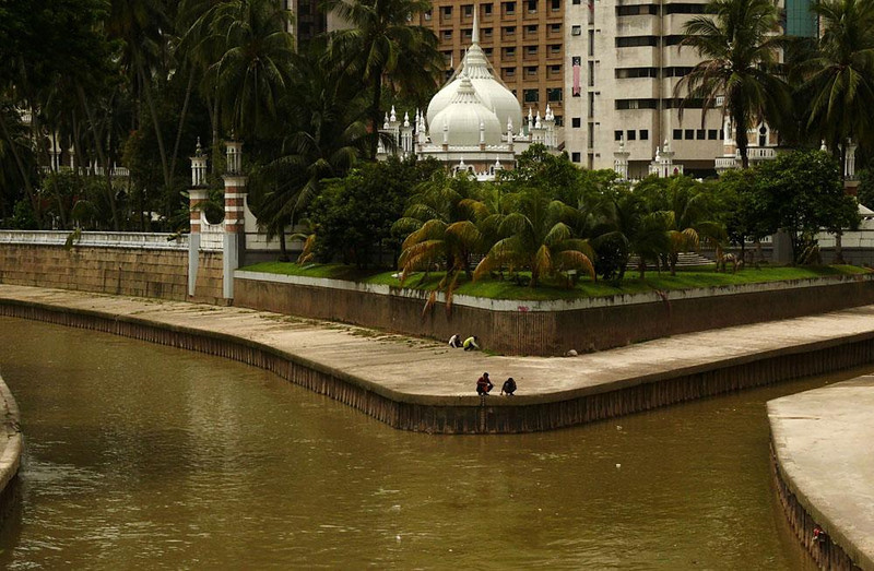 Confluence, Kuala Lumpur, Malaysia - Kuala Lumpur originated in the 1850s at the confluence of two rivers. They are still there today, only they now flow within banks of concrete. The domes of the Bandaraya Mosque rise in the background.