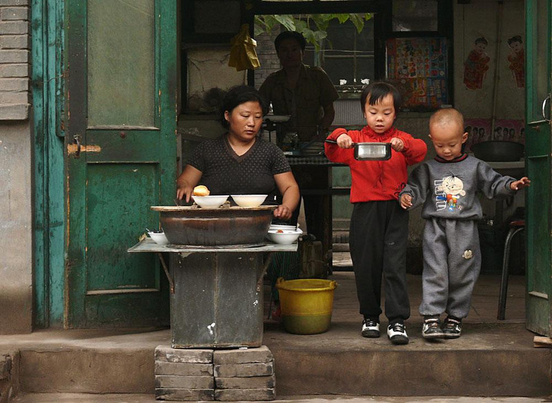 Breakfast coming, Pingyao, China - Breakfast is a family event in this Pingyao household. All four members are playing a part. I watched as the young girl in red, accompanied by her young brother, gently carried the hot pot out the door and down a neighboring street. As she vanished around a corner she looked back at me and smiled.