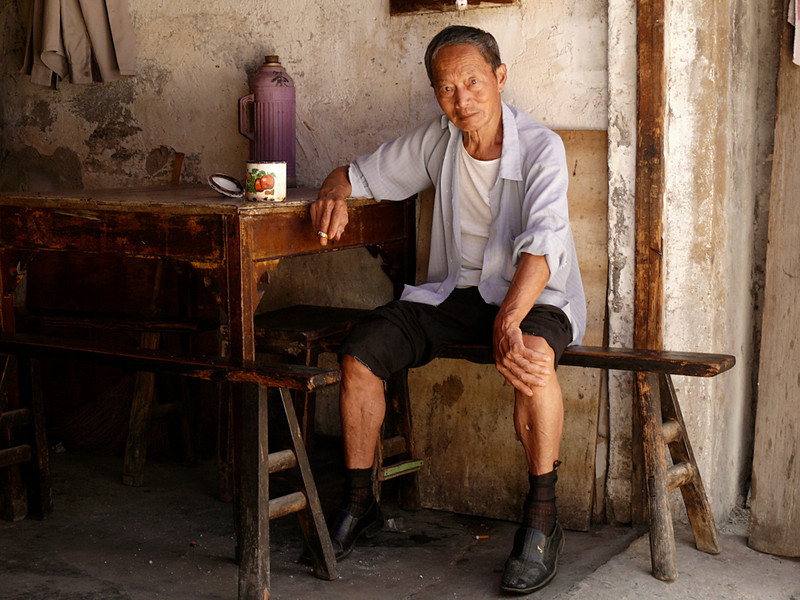 Portrait, Feng Jing, China - I particularly liked the narrow, high bench he sits upon. In spite of the fact that his heels are lifted off the ground and he has limited seating space, he seems perfectly at home here.