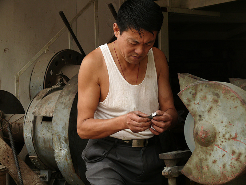 Precision grinding, Nanjing, China - A street-side grinder appraises his work. There are many such skills on display in the streets of this city.