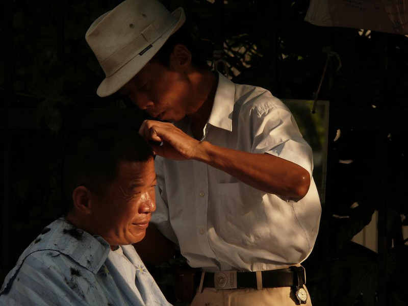 Haircut, Shanghai, China - I made this image in the French Concession, a area of Shanghai that was once governed by France. The barber works on the city sidewalk, using the day's last light to ply his craft.